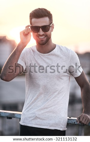 Casual and stylish. Smiling young man adjusting eyewear and looking at camera while standing outdoors - stock photo