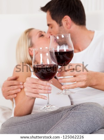 Casual attractive couple relaxing at home toasting each other with large glasses of red wine - stock photo