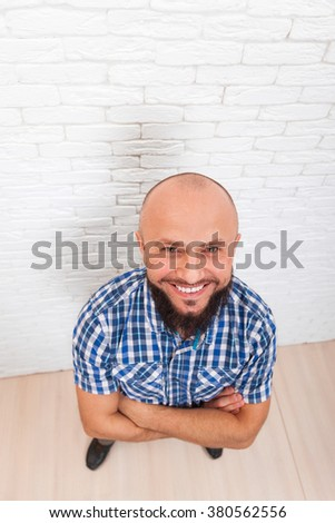 Casual Bearded Business Man Smiling Folded Hands Top View Office Over White Brick Wall - stock photo