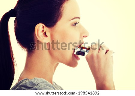 Casual beautiful woman trying to eat blister of pills. - stock photo