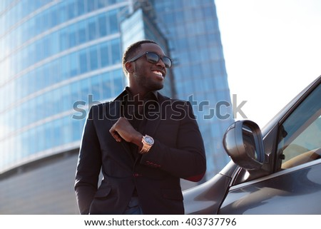 Casual black man in sunglasses posing near car in town. - stock photo