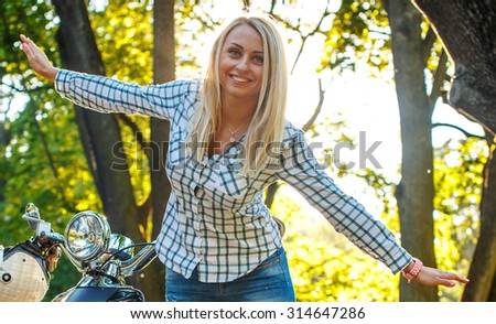 Casual blond woman in jeans and shirt possing near moto scooter in city park.