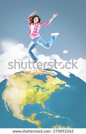 Casual brunette jumping and smiling against night sky - stock photo
