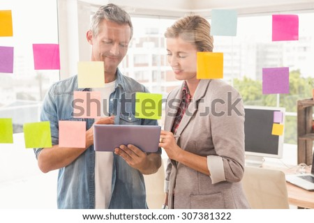 Casual business colleagues working with tablet in the office - stock photo
