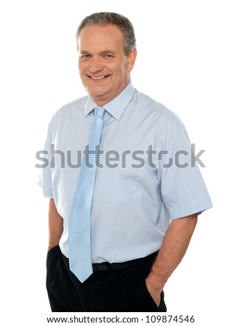 Casual business executive with hands in pocket smiling at camera - stock photo