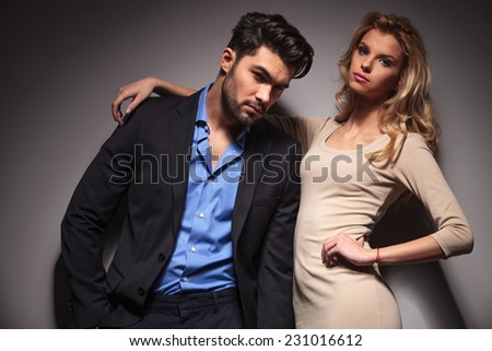 Casual business man leaning on his girlfriend, both looking at the camera.