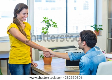 Casual business partners shaking their hands in the office - stock photo