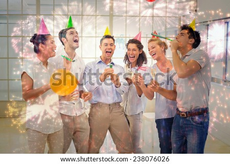 Casual business team celebrating with champagne and party poppers against colourful fireworks exploding on black background - stock photo