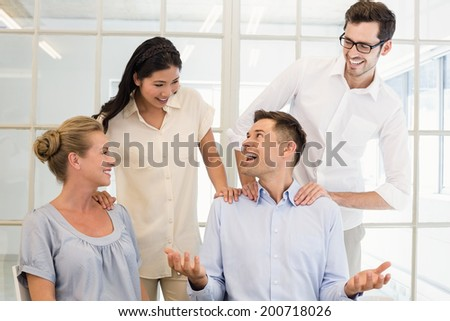 Casual business team congratulating colleague in the office - stock photo
