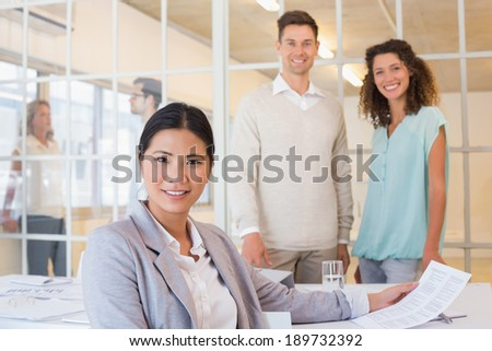 Casual business team having a meeting smiling at camera in the office