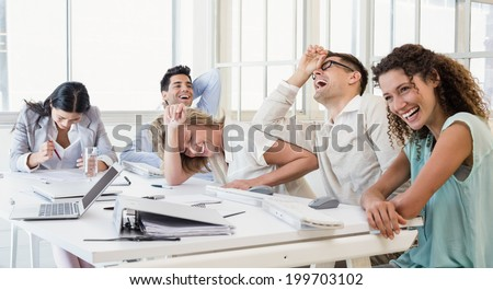 Casual business team laughing during meeting in the office - stock photo