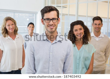 Casual business team smiling at camera in the office - stock photo