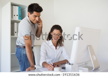 Casual business team working together at desk in the office