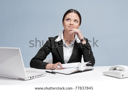 Casual business woman in office working with white table, laptop and diary personal organizer. Dreaming