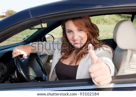 Casual business woman smiling on a car - stock photo