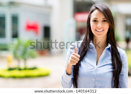 Casual business woman with thumbs up looking happy - stock photo