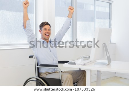 Casual businessman in wheelchair cheering at his desk in the office - stock photo