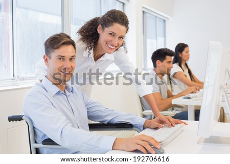 Casual businessman in wheelchair working at his desk with colleague in the office - stock photo