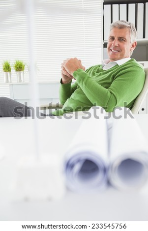 Casual businessman looking at camera in his office - stock photo