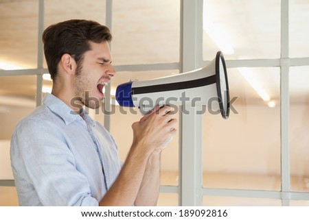 Casual businessman shouting through megaphone in his office