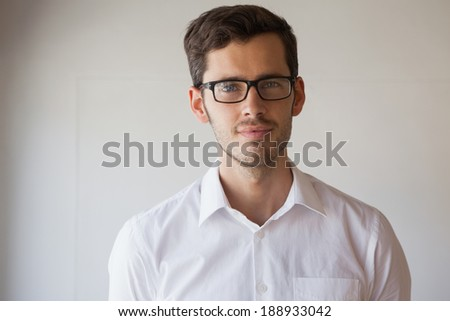 Casual businessman smiling at camera wearing glasses in the office - stock photo