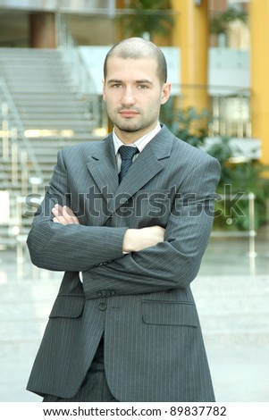 Casual businessman standing with crossed hands  in corporate office