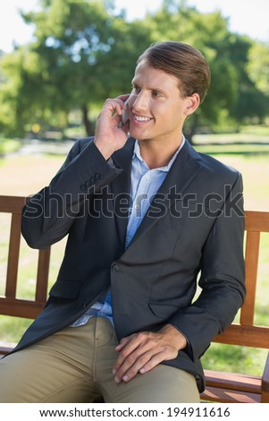 Casual businessman talking on phone on park bench on a sunny day
