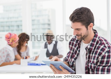 Casual businessman using digital tablet with colleagues behind him - stock photo