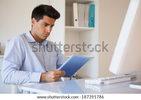 Casual businessman using his tablet at his desk in his office