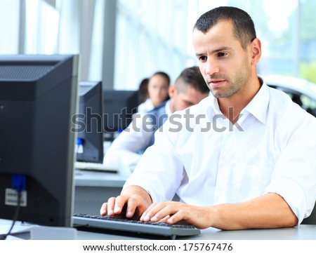 Casual businessman using laptop in office, sitting at desk, typing on keyboard  - stock photo