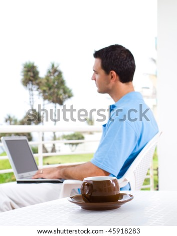 casual businessman using laptop on balcony with sea view behind, focus on the coffee cup - stock photo