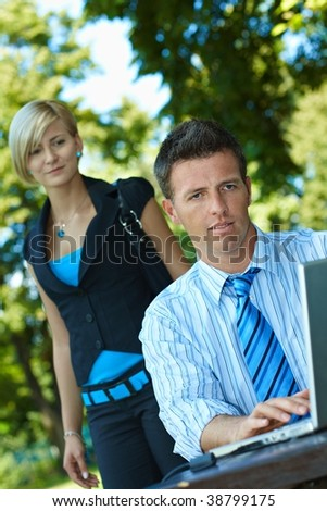 Casual businessman using laptopn in park summertime, young woman watching from behind.