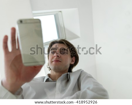 Casual businessman using mobile phone at modern stylish office, smiling. shot thrugh glass table, low angle