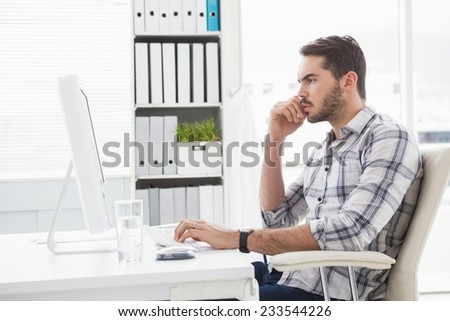 Casual businessman working at his desk in his office - stock photo