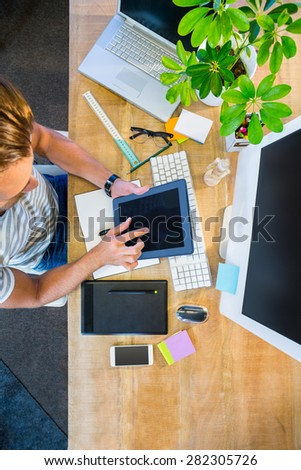 Casual businessman working on tablet at his desk - stock photo