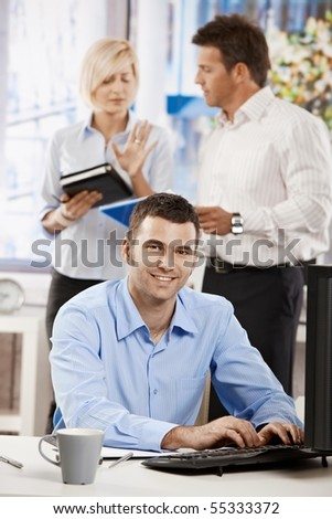 Casual businessman working with computer in office, looking at camera, smiling. - stock photo