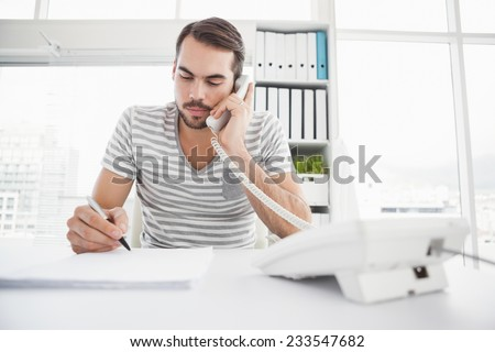 Casual businessman writing and phoning at his desk in his office - stock photo