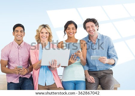 Casual businesspeople using digital tablet with colleagues behind in office against blue vignette background - stock photo
