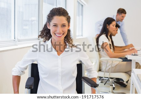 Casual businesswoman in wheelchair smiling at camera in the office - stock photo