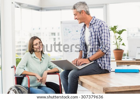 Casual businesswoman in wheelchair talking with colleague in the office - stock photo