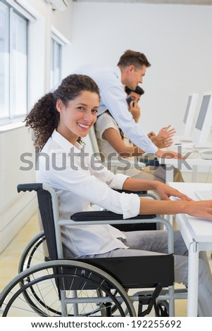 Casual businesswoman in wheelchair working at her desk in the office - stock photo