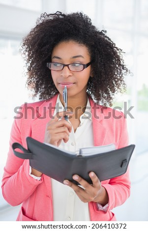 Casual businesswoman looking in her diary in her office - stock photo