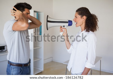 Casual businesswoman shouting at colleague through megaphone in the office - stock photo