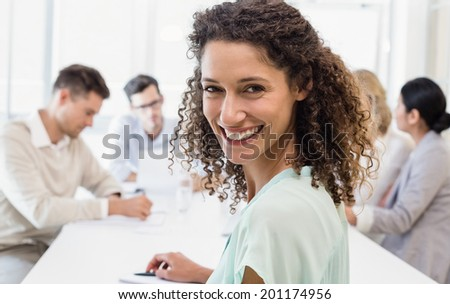 Casual businesswoman smiling at camera during meeting in the office