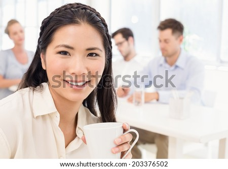 Casual businesswoman smiling at camera during meeting in the office - stock photo