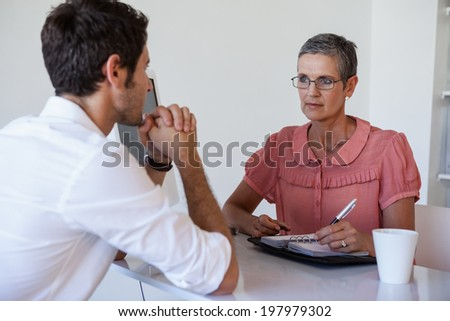 Casual businesswoman talking with colleague in the office - stock photo