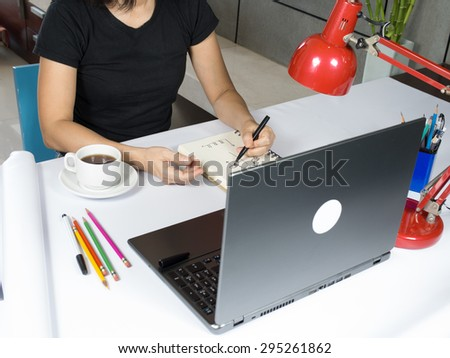 Casual businesswoman writing on notebook with coffee cup, laptop computer - stock photo