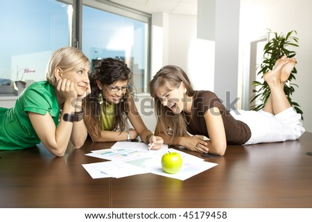 Casual businesswomen lying on table in meeting room, discussing business charts on paper. - stock photo