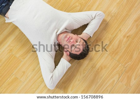 Casual calm man lying on floor with closed eyes in bright room - stock photo