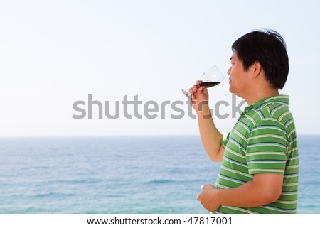 casual chinese man drinking wine and viewing seascape - stock photo